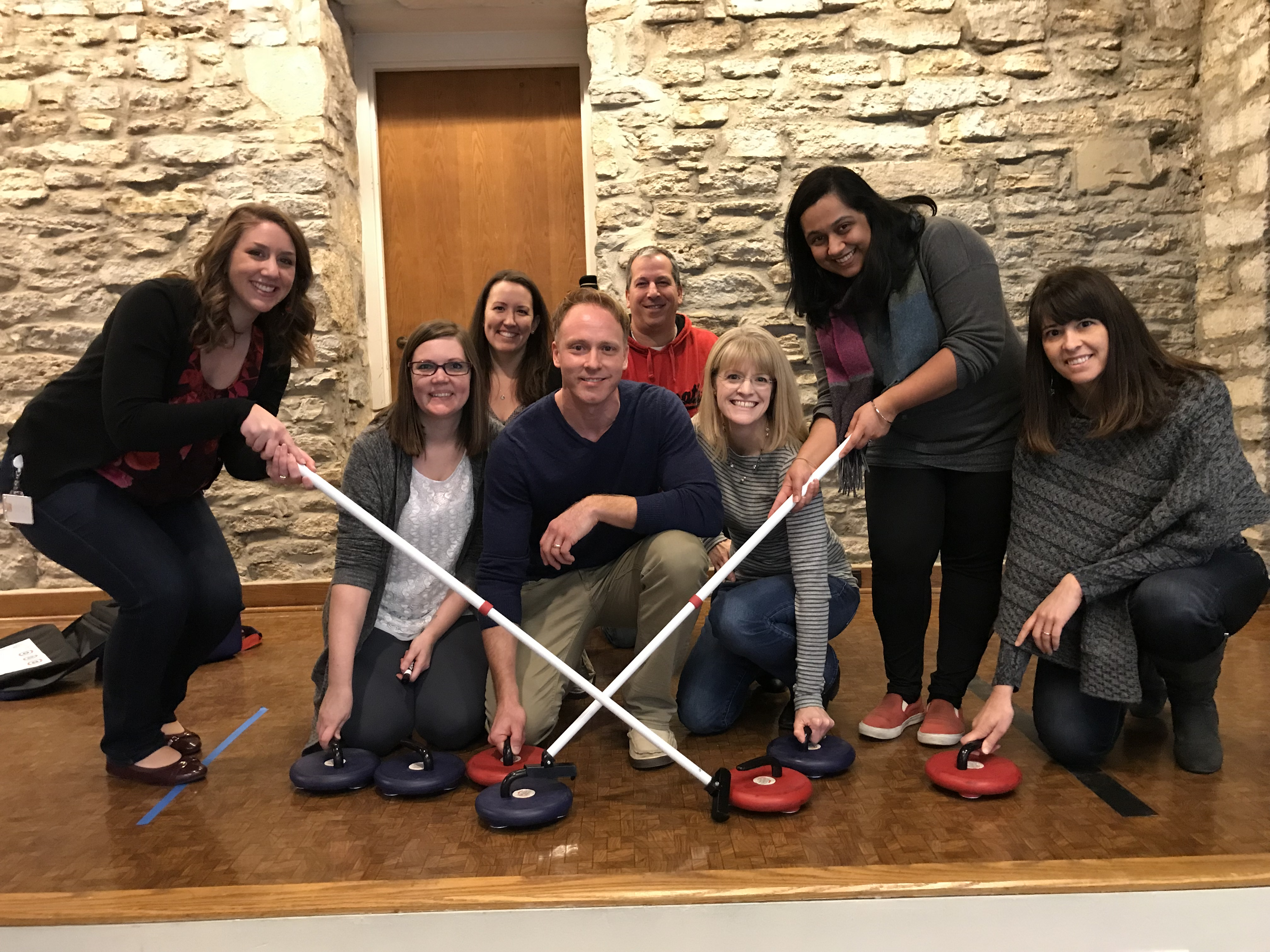employees playing curling, office olympics, culture