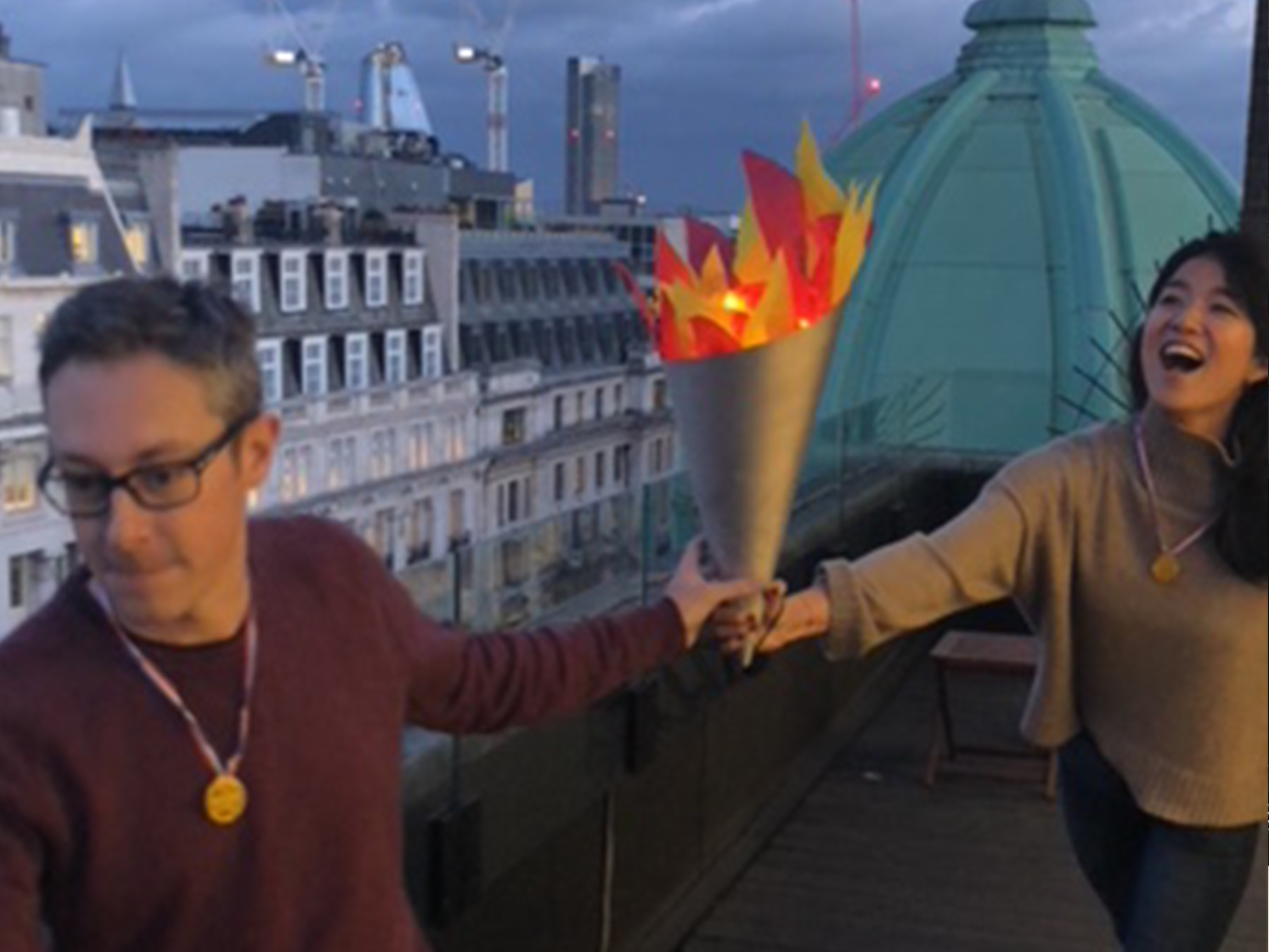 woman handing torch to colleague, London, office olympics, culture